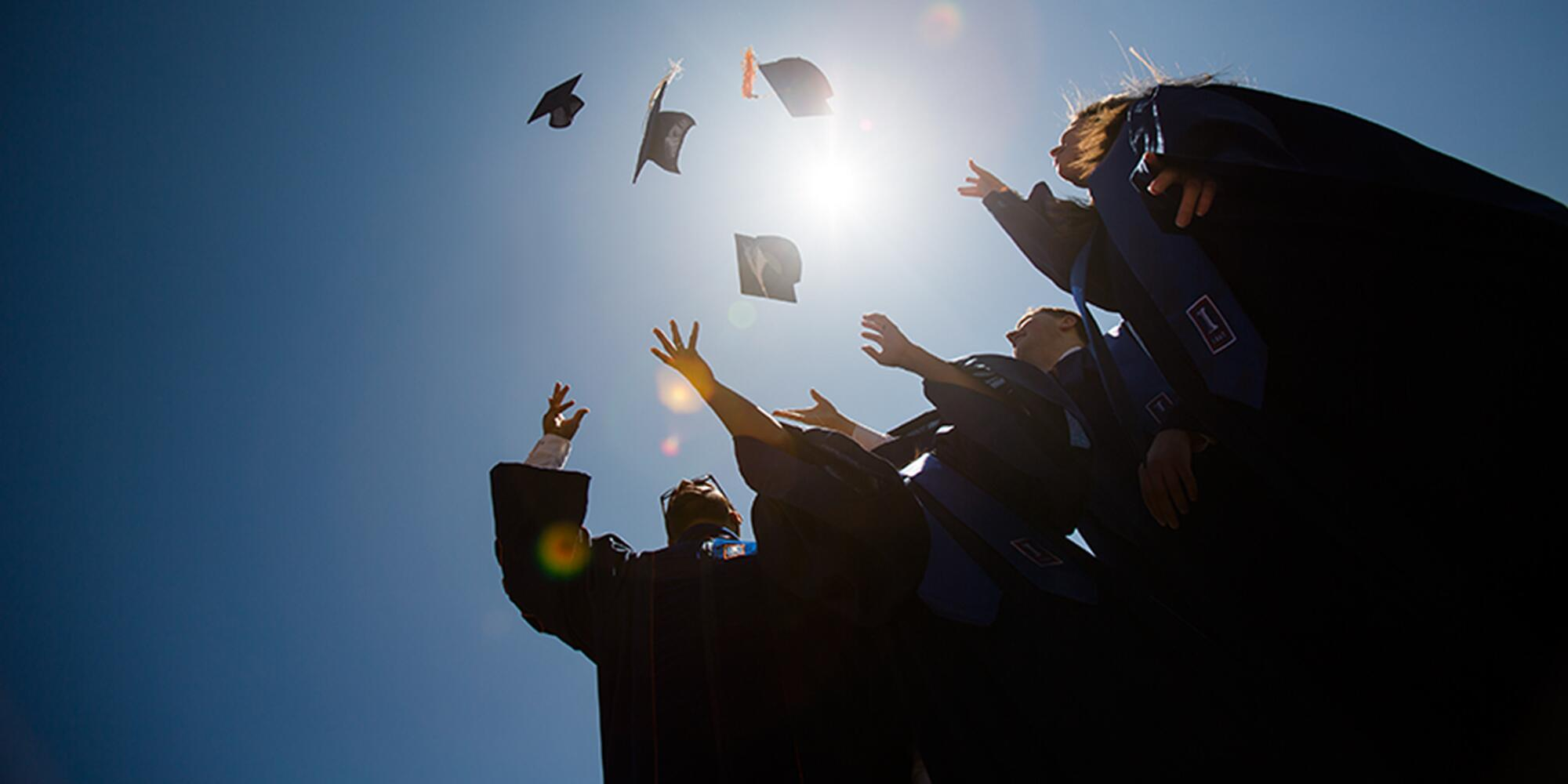Students toss their graduation caps into the air.