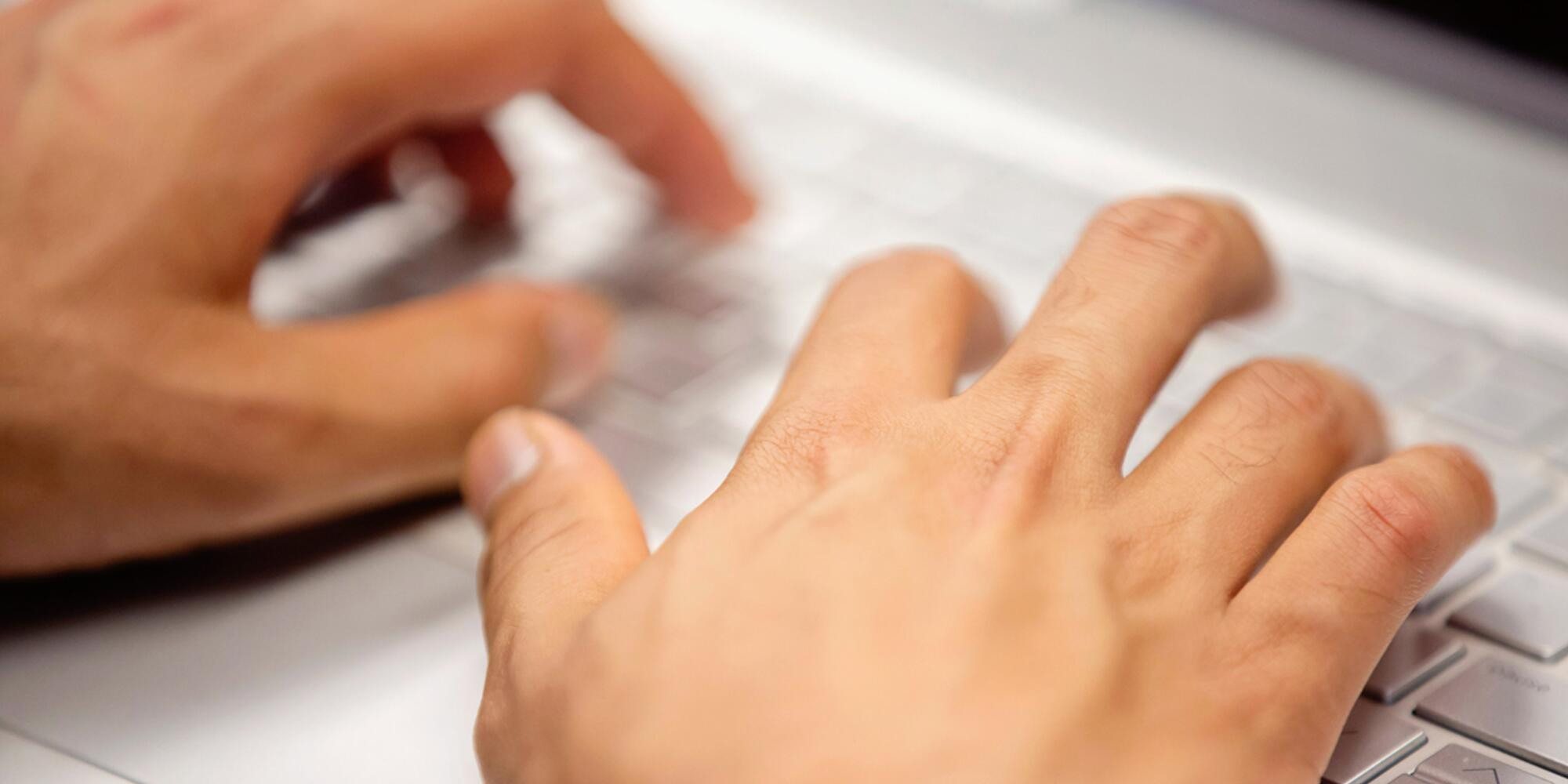 Photo of hands typing on a keyboard.