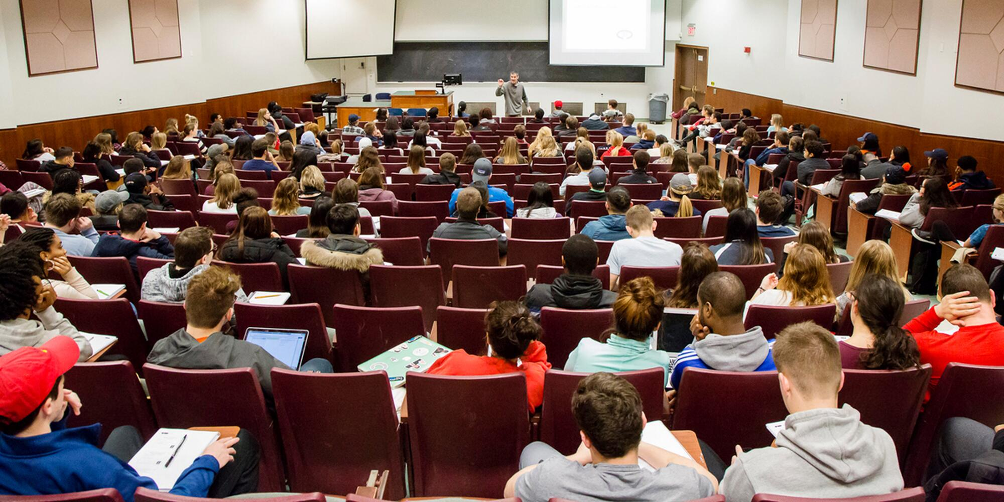 Photo taken from the back of a lecture hall, with rows of students watching a professor speak.