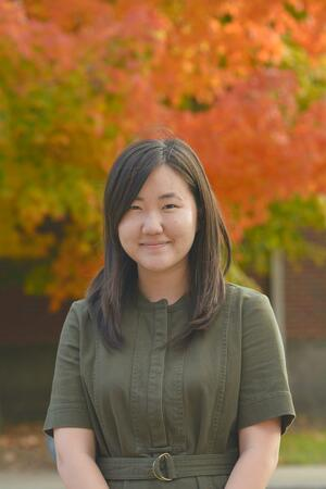 A photo of Jacqueline Yi. She is smiling at the camera and wearing a green shirt. Behind her are autumn trees.