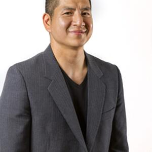 An image of Eric Tang. He is visible from the waist up, and wears a gray blazer over a black shirt. His hair is cut short. He smiles at the camera.