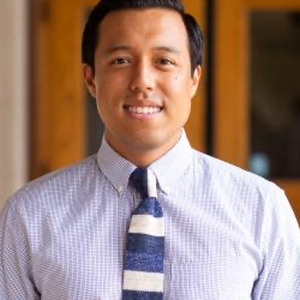 A photo of Dr. Leland Tabares. He is smiling at the camera, and wears a blue shirt and striped blue and white tie.